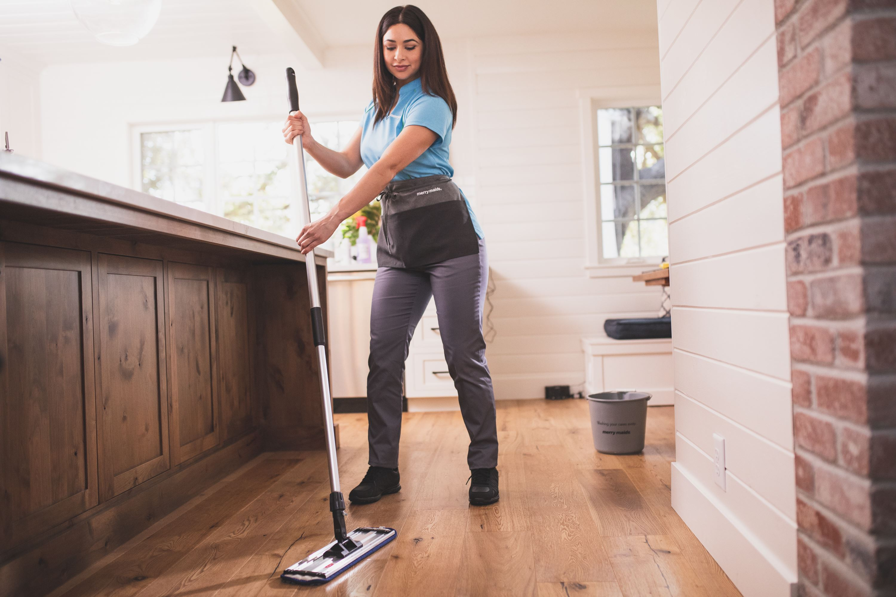 professional maid mopping wood floor
